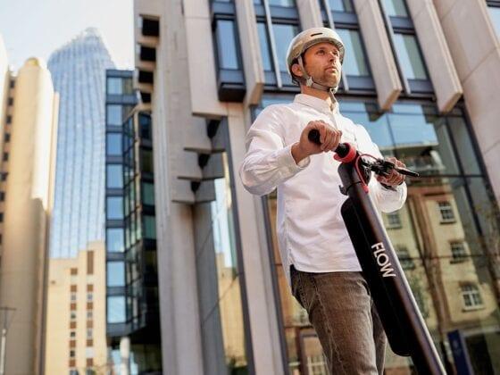 Man riding St-Kilda Flow electric scooter in city wearing Bern helmet