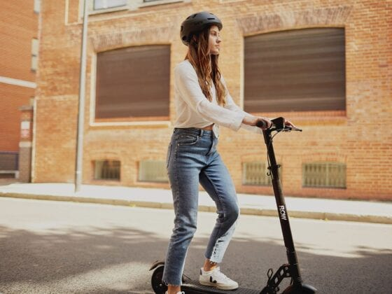 Woman riding Flow Electric Scooters in city