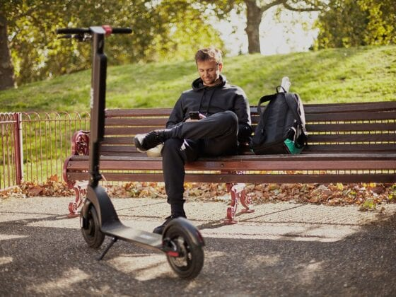 Man sitting on bench with Flow Electric Scooters in a park