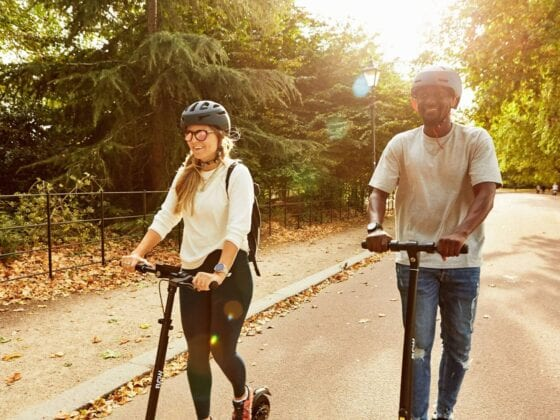 Couple riding Flow electric scooters in park